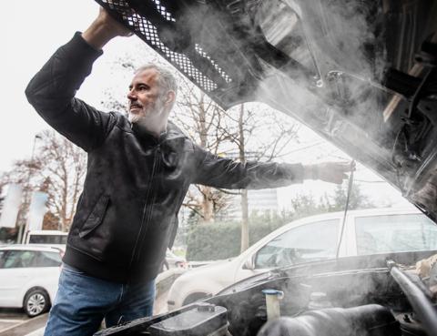 um senhor a levantar o capô do carro e a sair fumo do mesmo