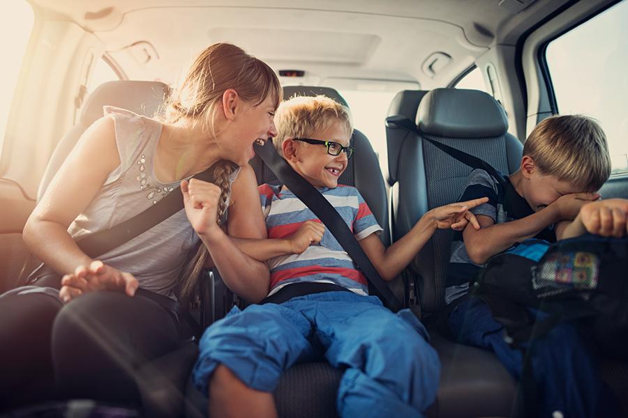 uma mãe a rir-se no banco traseiro do carro com os seus filhos