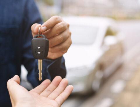 uma pessoa a dar uma chave do carro a outra